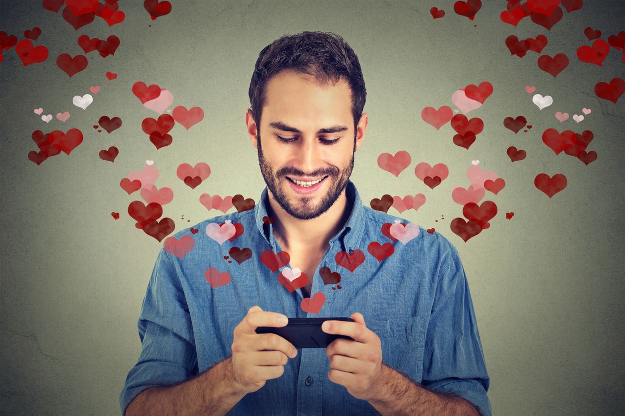 man sending love sms message on mobile phone