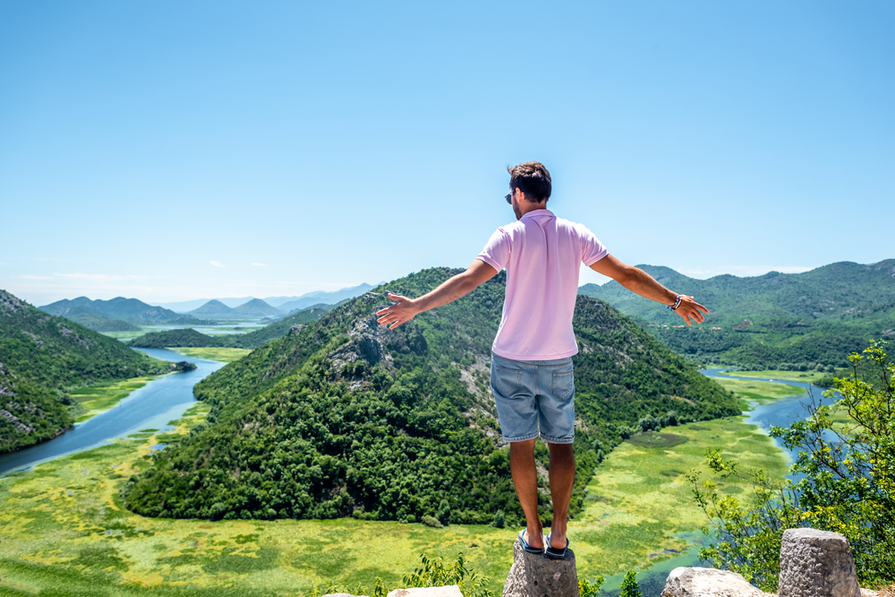 Man standing on a stone looking at a scenic countryside view